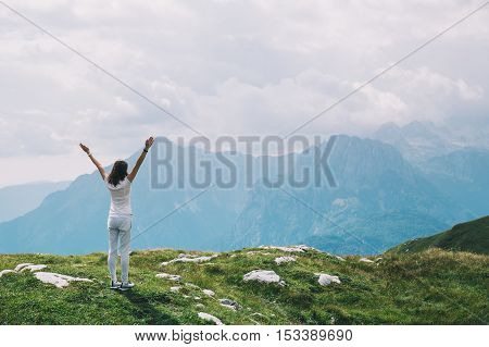Traveler or hiker with raised arms up in the mountains. Mangart is a mountain in the Julian Alps located between Italy and Slovenia. Travel Freedom Lifestyle concept.