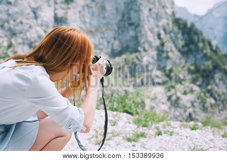 Traveler or hiker takes photos in the mountains. Mangart is a mountain in the Julian Alps located between Italy and Slovenia. Travel Freedom Lifestyle concept.
