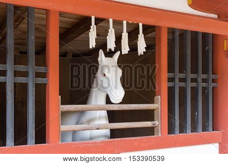 Hiroshima Japan - September 20 2016: All white stone statue of horse at itsukushima Shinto Shrine. Set in vermilion stable. Red-eyed Horse looks outside.