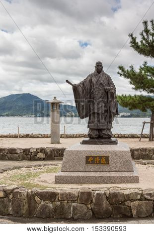 Hiroshima Japan - September 20 2016: Statue of Taira No Kiyomori 12th century military leader at the shore of Miyajima Island. He was the benefactor of the Itsukushima Shinto Shrine. Inland Sea in back.
