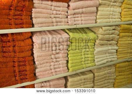 Background exact colorful shopping showcase shelves with many fluffy towels green yellow red and blue horizontal image (selective focus)