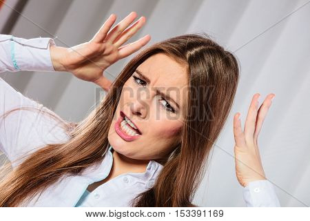 Handling stress and emotions in work. Frustrated female scream feel anger and pain. Hands in air and open mouth. Formal dressed woman with headache.