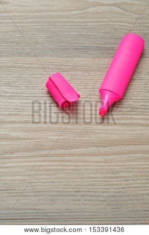 Pink highlighter isolated on a wooden background