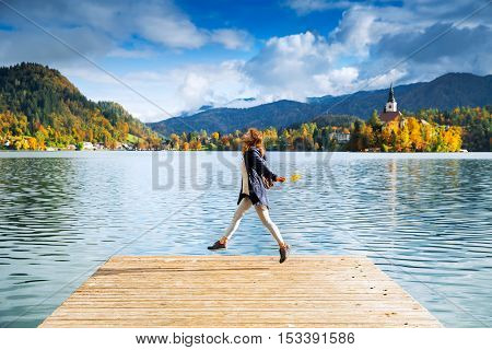 Beautiful woman jumping on a wooden pier on the background with Bled Castle and Church on the Island on the Lake Bled Slovenia. Autumn time in Europe.