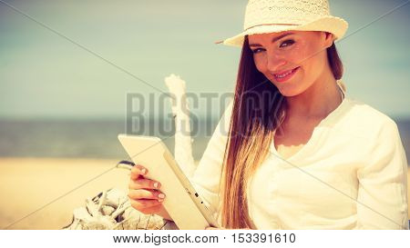 Technology enjoyment. Long haired beauty girl in straw hat with tablet e-book on beach. Student woman resting in summer on fresh air.