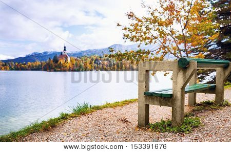 View On Bled Lake. Autumn in Slovenia Europe. View on Island with Catholic Church in Bled Lake with Autumn Forest and Mountains in Background.
