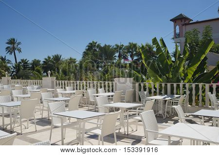 Empty cafe on the terrace on a summer day, without guests, white chairs and tables, selective focus