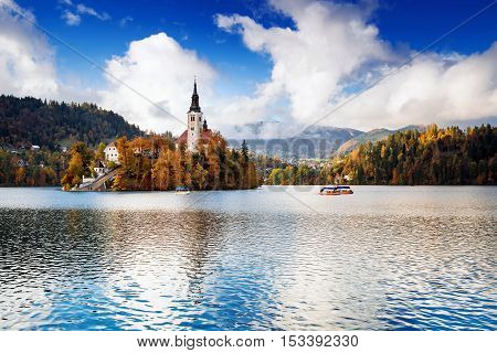 Amazing View On Bled Lake. Autumn in Slovenia Europe. View on Island with Catholic Church in Bled Lake with Autumn Forest and Mountains in Background.