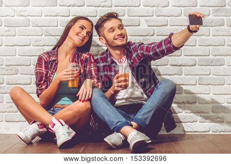 Stylish teenage couple is drinking juice doing selfie using a smart phone and smiling sitting on the floor on white brick wall background