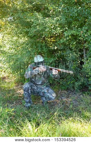 Hunter in wooded area looking through sights at target down range