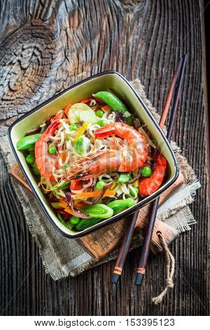 Chinese noodles vegetables and prawns on old wooden table
