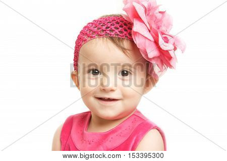 Cute Baby Girl in a Pink Dress and Headband with a big Flower on a white background
