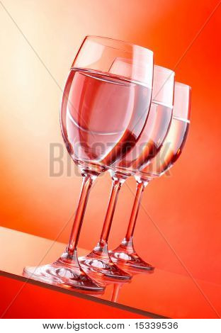 Three wine glasses on red background