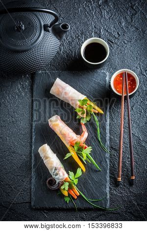 Fresh spring rolls with soy sauce on black rock
