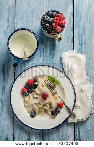 Delicious and fresh dumplings with fruits on old wooden table