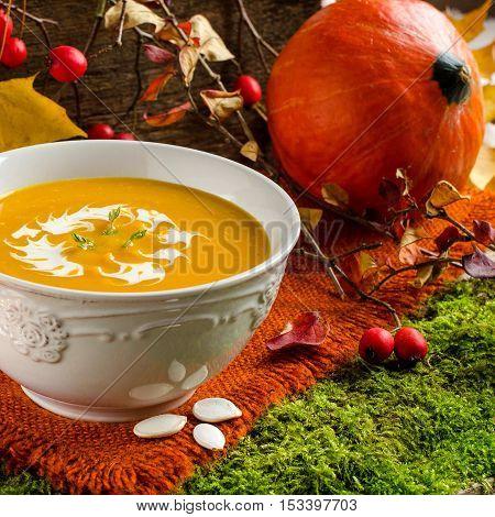 Orange round pumpkin. Pumpkin soup. White vintage plate. Orange napkin. Pumpkin seeds. Background - old Board.
