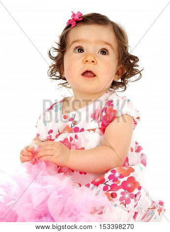 Cute baby girl on a white background wearing a pretty dress and she is playing with a pink feather boa.