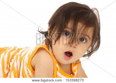 Funny Baby Girl on a white background with long brown hair and brown eyes.  Her hair is in her eyes and her mouth is open.