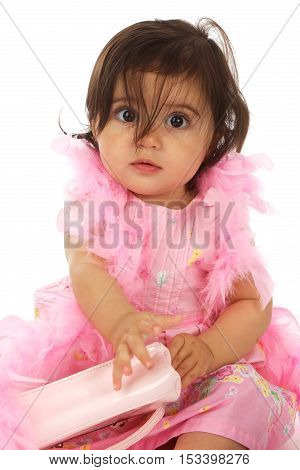 Funny Baby Girl on a white background with long brown hair and brown eyes.  She is wearing all pink with a feather boa and a purse.  Her hair is hanging in her eyes