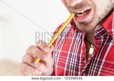 bearded man on a red checked shirt biting a pencil until a solution has been found and there is lots of copyspace