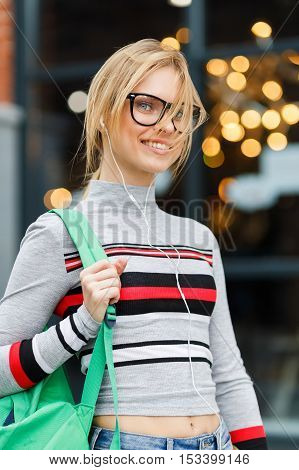 Student with glasses and headphones on background of glass door of building
