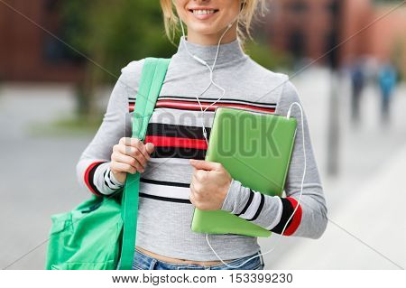 Girl with backpack and tablet in her hands on blurred background