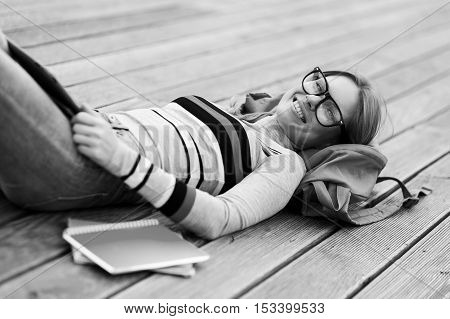 Smiling girl in glasses rested on wooden floor. black and white photo