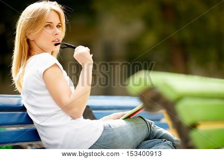 Dreamy girl with glasses at park bench