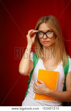 Blonde with glasses and book in hands on empty Brown background