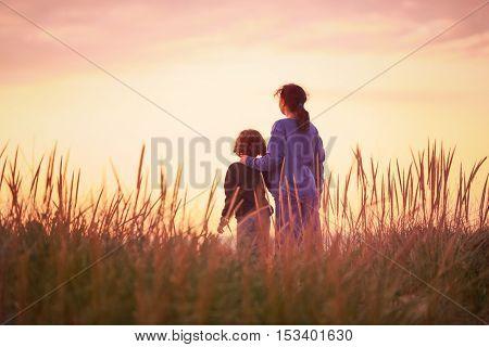 Girls watching the beautiful sunset at the beach