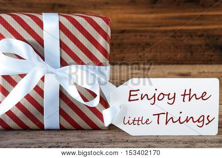 Macro Of Christmas Gift Or Present On Wooden Background. Card For Seasons Greetings, Best Wishes Or Congratulations. White Ribbon With Bow. English Quote Enjoy The Little Things