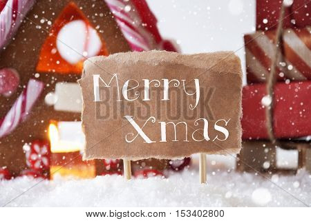 Gingerbread House In Snowy Scenery As Christmas Decoration. Sleigh With Christmas Gifts Or Presents And Snowflakes. Label With English Text Merry Xmas