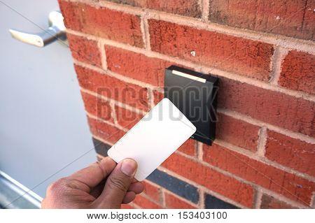 using white entrance card at door entrance card reader