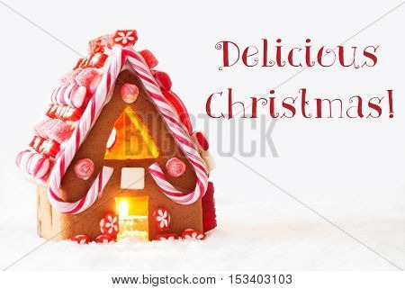 Gingerbread House In Snowy Scenery As Christmas Decoration With White Background. Candlelight For Romantic Atmosphere. English Text Delicious Christmas