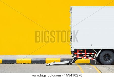 Delivery truck parking at footpath with yellow wall background and space for text