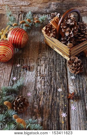 Christmas background: basket with cinnamon sticks and pine cones