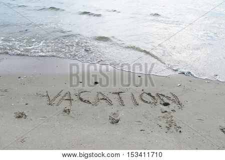 Writing on sand. Words on sand. Summer word on sand beach. Vacation words on sandy beach. Sandy beach background