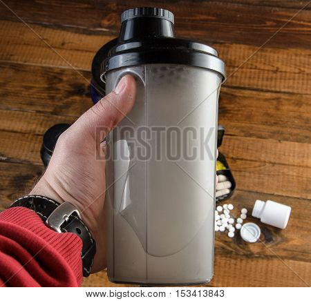 mans hand holding sport shaker. Sport and Fitness Supplement on a wood background