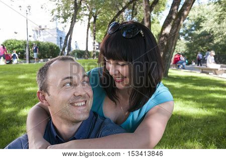 Woman hugging a man in the park on the grass