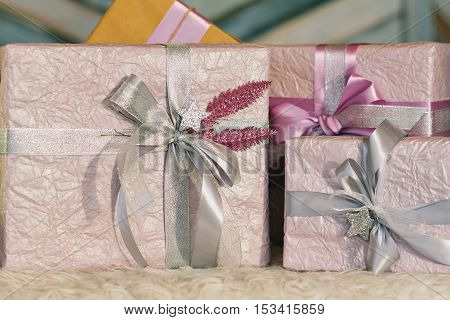 Holiday gift boxes decorated with ribbon. Beautiful purple shiny package for Christmas and New Year. Sebebryannaya tape.