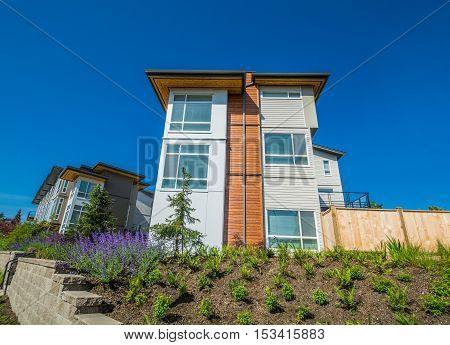 Brand new townhouse building on the hill with landscaped on sunny day in British Columbia