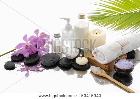 Tropical setting with palm ,towel, orchid, stones,oil
