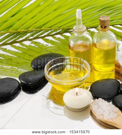 spa concept with palm ,towel, salt in spoon, stones, oil