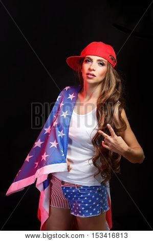 Young attractive girl in a baseball cap and sunglasses holding a US flag. She a T-shirt and shorts with a print of the flag. Long curly hair. Patriot country. She shows the victory.