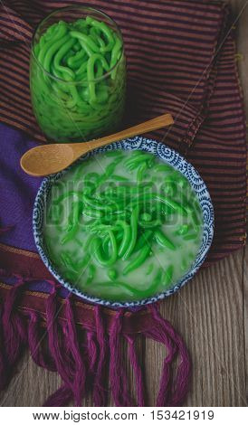 Lod Chong, Thai Dessert on Thai Textile with Wood Background Rice Noodles Made of Rice Eaten with Coconut Cream