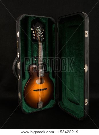 Mandolin in a black case on a dark background Mandolin