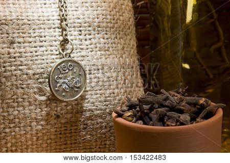 Clove spice and zodiac sign on a background of burlap