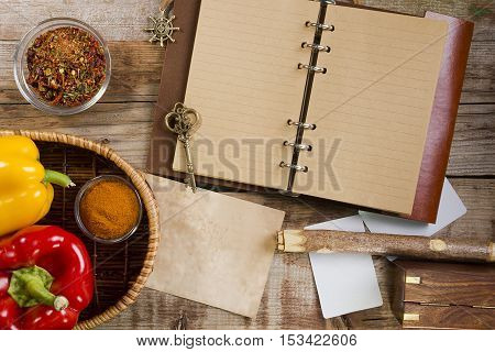 Diary for records and paprika on old wooden background