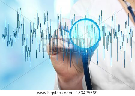 Electrocardiogram and female hand with stathoscope, closeup. Cardiology concept.