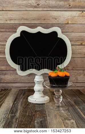 Blank chalkboard sign and a pumpkin muffin on a glass stand